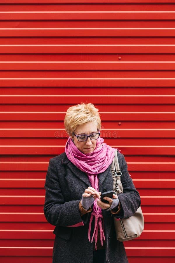 Ενήλικη γυναίκα με το smartphone στην οδό στοκ φωτογραφία