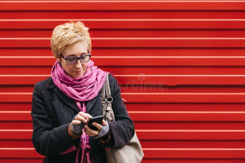Ενήλικη γυναίκα με το smartphone στην οδό στοκ εικόνες με δικαίωμα ελεύθερης χρήσης