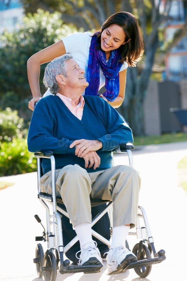 Ενήλικη κόρη που ωθεί τον ανώτερο πατέρα στην αναπηρική καρέκλα στοκ εικόνες