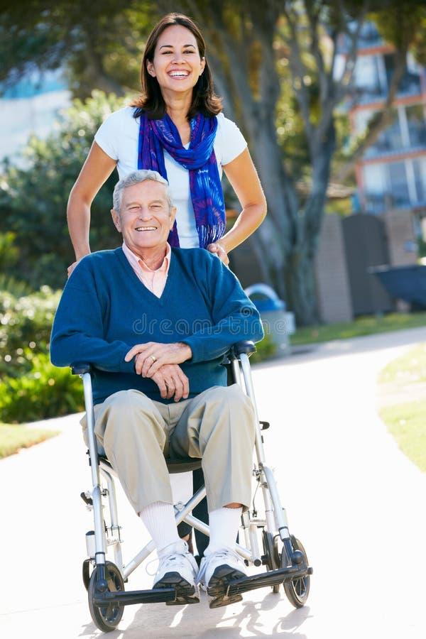 Ενήλικη κόρη που ωθεί τον ανώτερο πατέρα στην αναπηρική καρέκλα στοκ φωτογραφίες