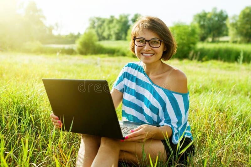 Ενήλικη eautiful γυναίκα που χρησιμοποιεί το lap-top υπαίθρια στοκ εικόνα με δικαίωμα ελεύθερης χρήσης