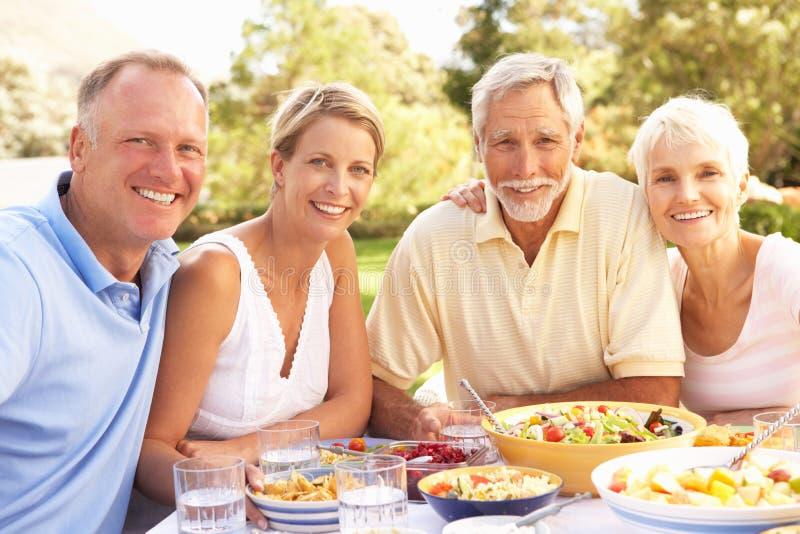 Ενήλικοι γιος και κόρη που απολαμβάνουν το γεύμα στον κήπο στοκ εικόνες