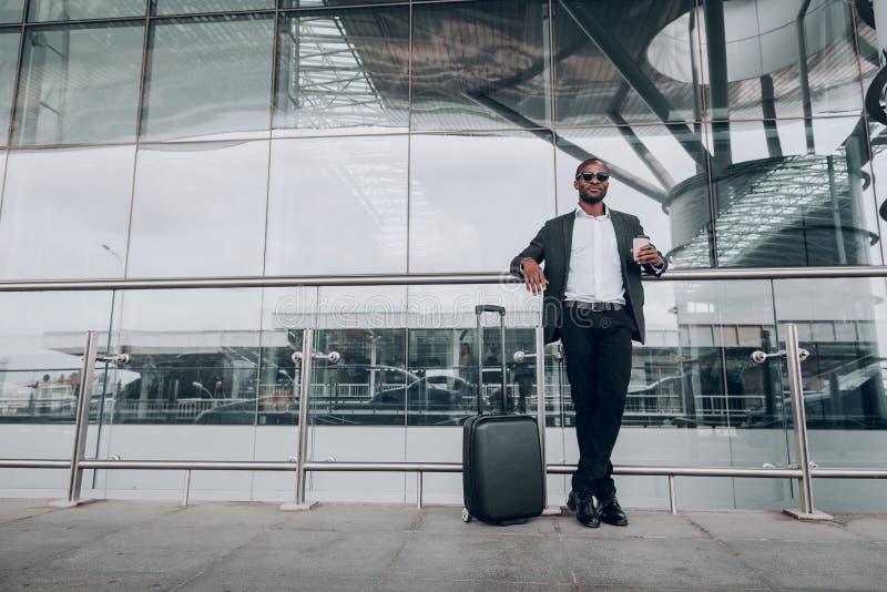 Ενήλικος επιχειρηματίας που στέκεται δίπλα στο φλιτζάνι του καφέ εκμετάλλευσης αερολιμένων