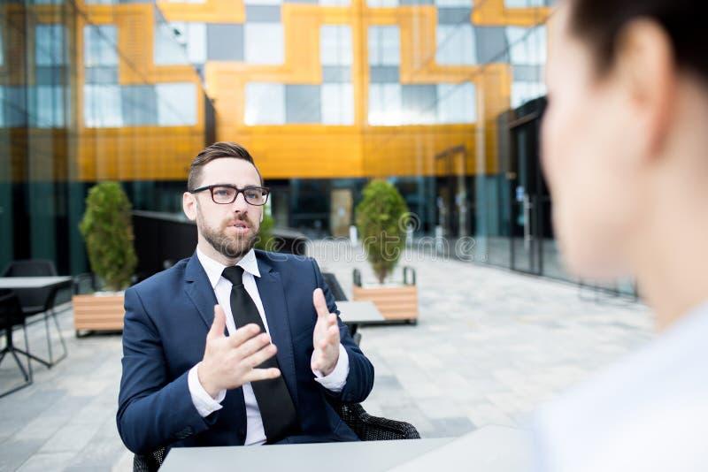 Ενήλικος επιχειρηματίας στο πεζούλι που μιλά στο συνάδελφο στοκ εικόνες