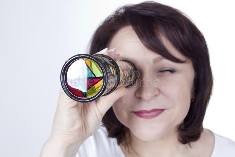 Ενήλικη γυναίκα που εξετάζει ένα καλειδοσκόπιο στοκ εικόνες