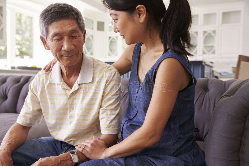 Ενήλικη κόρη που μιλά στον καταθλιπτικό πατέρα στο σπίτι στοκ φωτογραφίες