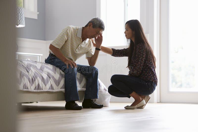Ενήλικη κόρη που μιλά στον καταθλιπτικό πατέρα στο σπίτι στοκ εικόνα