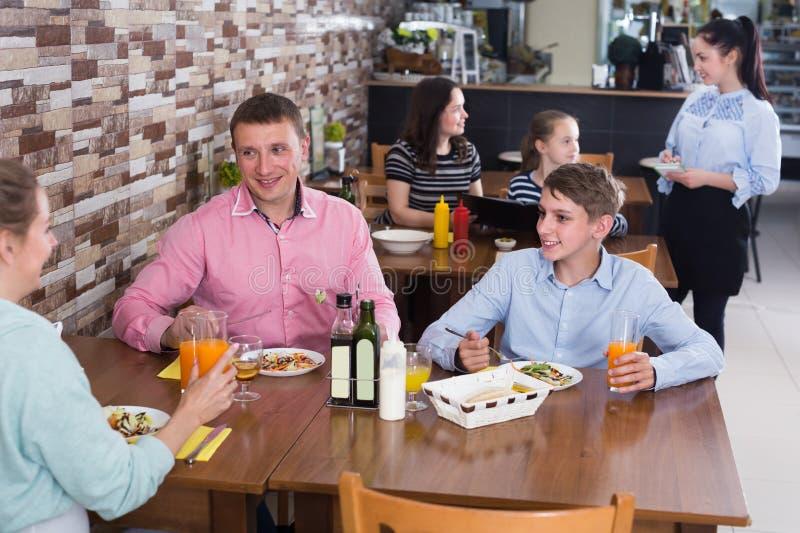 Ενήλικη οικογένεια με τους εφήβους που έχουν το μεσημεριανό γεύμα στοκ φωτογραφία