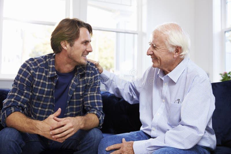 Ενήλικη συνεδρίαση γιων στον καναπέ και ομιλία στον πατέρα στο σπίτι στοκ εικόνα