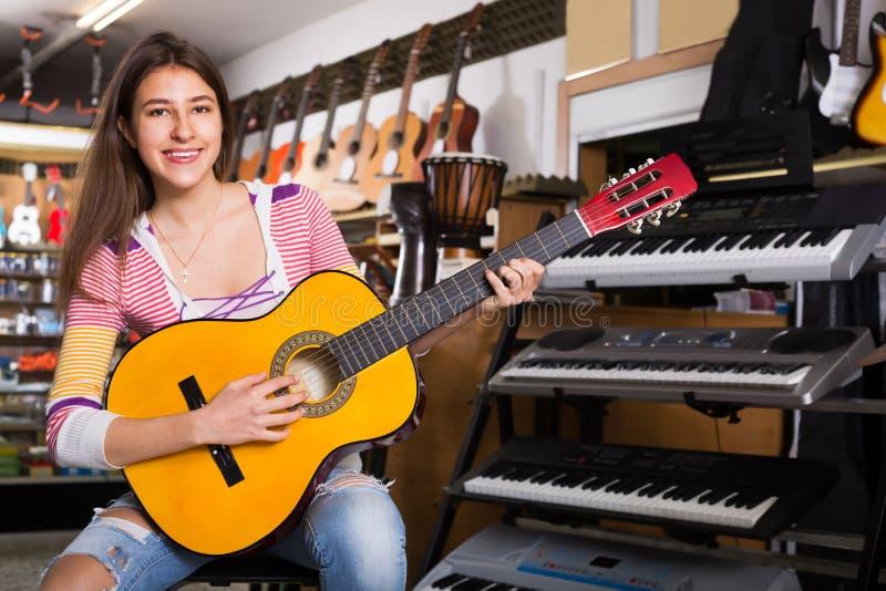 Ενήλικος θηλυκός πελάτης που προσπαθεί να παίξει τη νέα κιθάρα στοκ εικόνα