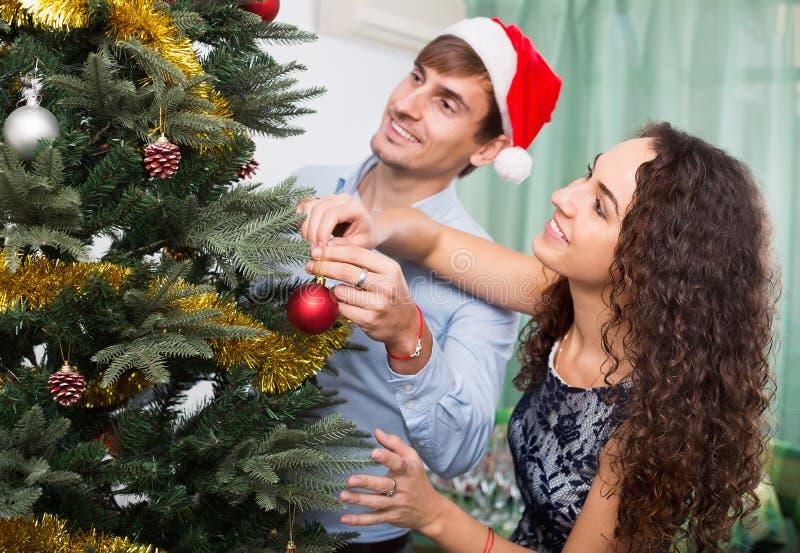 Ενήλικο ευτυχές ζεύγος που διακοσμεί το χριστουγεννιάτικο δέντρο στοκ φωτογραφία με δικαίωμα ελεύθερης χρήσης