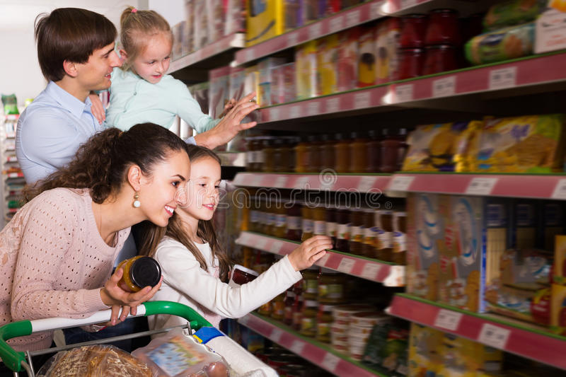 Ενήλικο ζεύγος με τα μικρά παιδιά που αγοράζουν τη μαρμελάδα στοκ εικόνα