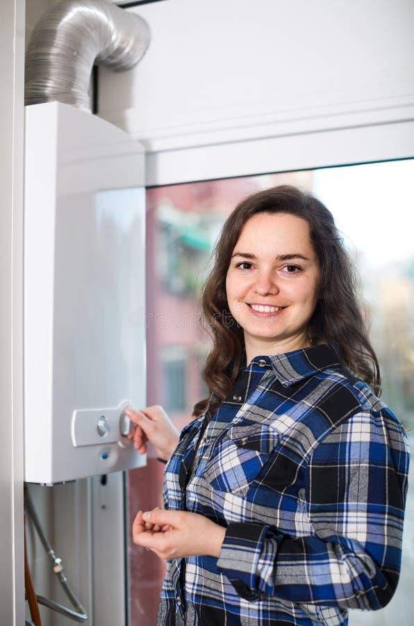 Ενήλικο κορίτσι στο πουκάμισο κοντά στο πίνακα ελέγχου λεβήτων στοκ φωτογραφία