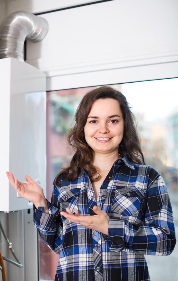 Ενήλικο κορίτσι στο πουκάμισο κοντά στο πίνακα ελέγχου λεβήτων στοκ εικόνα