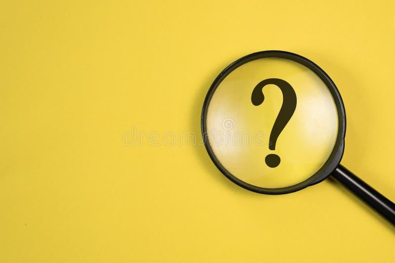 Ενίσχυση - γυαλί με το ΕΡΩΤΗΜΑΤΙΚΌ στην εστίαση στο κίτρινο υπόβαθρο στοκ εικόνα