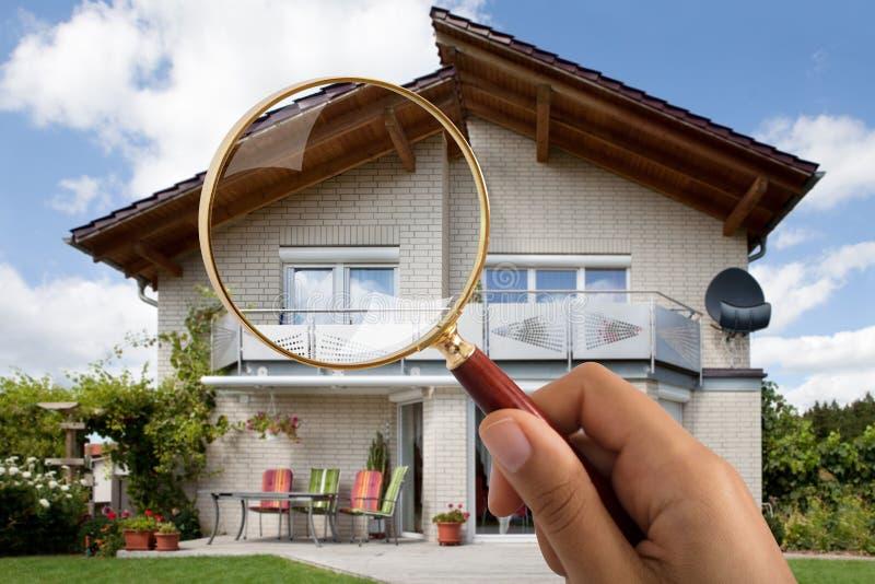 Ενίσχυση εκμετάλλευσης χεριών προσώπων ` s - γυαλί πέρα από το σπίτι πολυτέλειας στοκ φωτογραφία