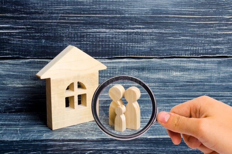 Ενίσχυση - το γυαλί εξετάζει την οικογένεια στέκεται κοντά στο σπίτι Ξύλινοι αριθμοί της στάσης προσώπων κοντά σε ένα ξύλινο σπίτ στοκ φωτογραφίες