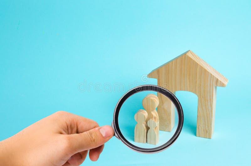 Ενίσχυση - το γυαλί εξετάζει τη νέα οικογένεια με τα παιδιά στέκεται κοντά σε ένα ξύλινο σπίτι Η έννοια μιας ισχυρής οικογένειας στοκ φωτογραφία