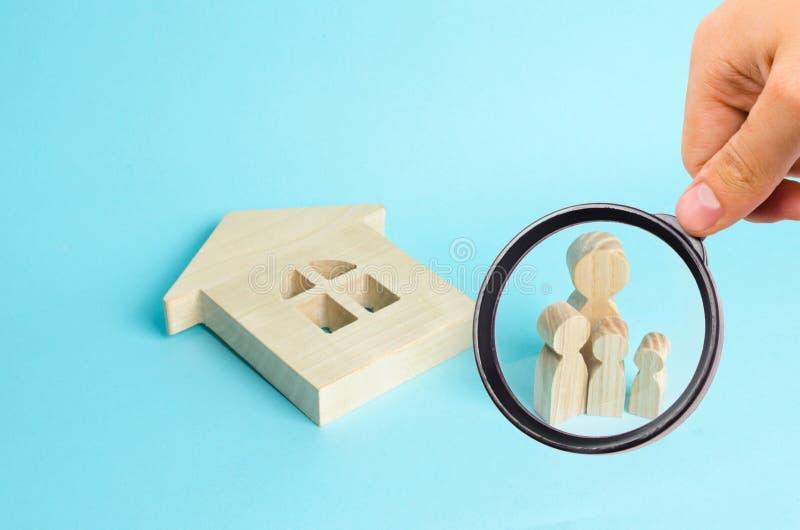 Ενίσχυση - το γυαλί εξετάζει τις οικογενειακές στάσεις κοντά στο πεσμένο σπίτι Αγοράζοντας άστεγη οικογένεια ακινησίας στοκ φωτογραφία με δικαίωμα ελεύθερης χρήσης