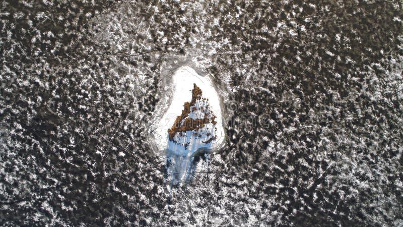 Εναέρια άποψη από τον κηφήνα ενός μικρού νησιού στη λειώνοντας λίμνη πάγου στοκ εικόνες με δικαίωμα ελεύθερης χρήσης