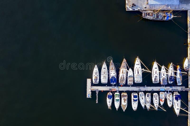 Εναέρια άποψη από τον κηφήνα των γιοτ και των μικρών βαρκών μηχανών Άσπρες βάρκες στο θαλάσσιο νερό στοκ εικόνα