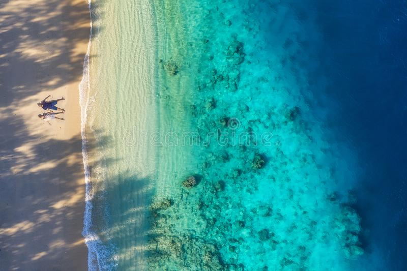 Εναέρια άποψη ενός ζεύγους ανθρώπων στην παραλία Διακοπές και περιπέτεια Παραλία και τυρκουάζ νερό Τοπ άποψη από τον κηφήνα στην  στοκ φωτογραφία με δικαίωμα ελεύθερης χρήσης