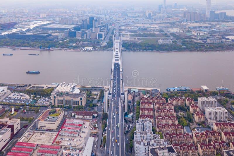 Εναέρια άποψη μιας γέφυρας με το στο κέντρο της πόλης ορίζοντα της Σαγκάη ποταμών Huangpu, Κίνα Κτήρια στη κατοικήσιμη περιοχή στοκ εικόνα
