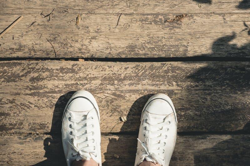 Εναέρια άποψη της άσπρης στάσης παπουτσιών καμβά πάνινων παπουτσιών στο παλαιό wo grunge στοκ εικόνα