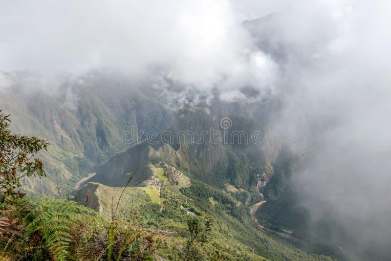 Εναέρια άποψη της ακρόπολης Machu Picchu Inca στα σύννεφα, που βρίσκεται σε μια κορυφογραμμή βουνών επάνω από την ιερή κοιλάδα στοκ εικόνες