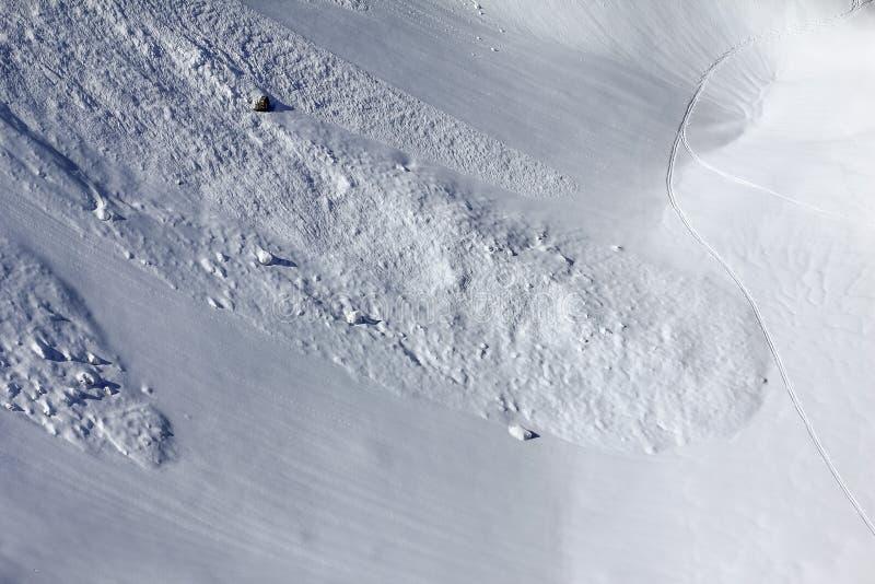 Εναέρια άποψη της κλίσης χιονιού με το ίχνος διαδρομής χιονοστιβάδων και σκι στοκ εικόνες με δικαίωμα ελεύθερης χρήσης