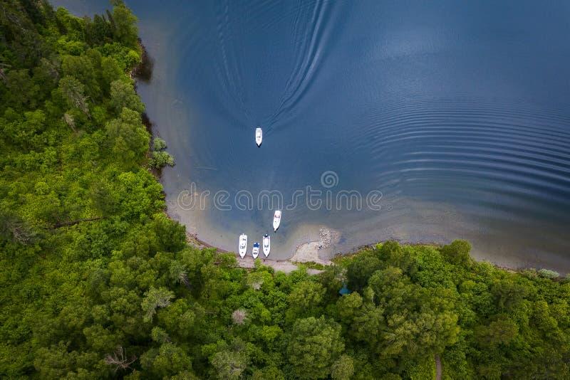Εναέρια άποψη της λίμνης με τις βάρκες κοντά στην ακτή και μια βάρκα που πλέουν στην αποβάθρα με τα πράσινα δέντρα στοκ φωτογραφία με δικαίωμα ελεύθερης χρήσης