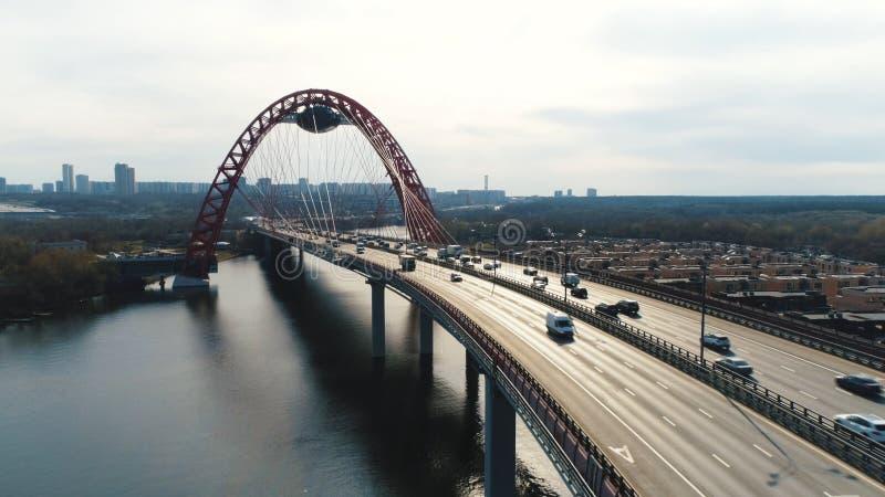Εναέρια άποψη της σύγχρονης καλώδιο-μένοντης γέφυρας μέσω του Μόσχα-ποταμού με την κίνηση των αυτοκινήτων ενάντια στο νεφελώδη ου στοκ φωτογραφίες