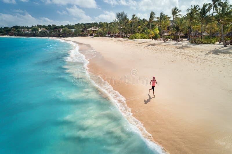 Εναέρια άποψη της τρέχοντας νέας γυναίκας στην αμμώδη παραλία στοκ φωτογραφία