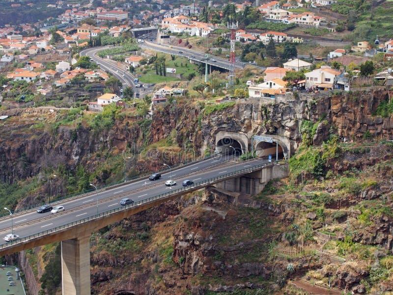 Εναέρια άποψη τοπίων της γέφυρας αυτοκινητόδρομων στο Φουνκάλ που εισάγει μια σήραγγα στην κοιλάδα με τα κτήρια και τις οδούς της στοκ εικόνα με δικαίωμα ελεύθερης χρήσης