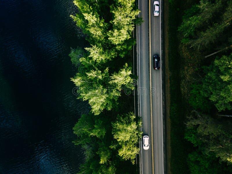 Εναέρια άποψη τοπίων του δρόμου μεταξύ της πράσινης δασικής και μπλε λίμνης πεύκων στη Φινλανδία στοκ εικόνα με δικαίωμα ελεύθερης χρήσης