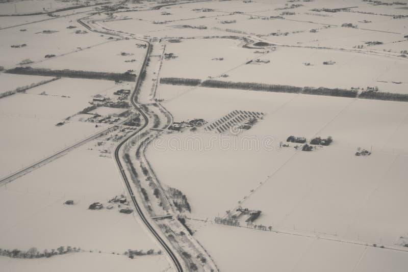 Εναέρια άποψη του αγροκτήματος και του δρόμου το χειμώνα στοκ φωτογραφίες