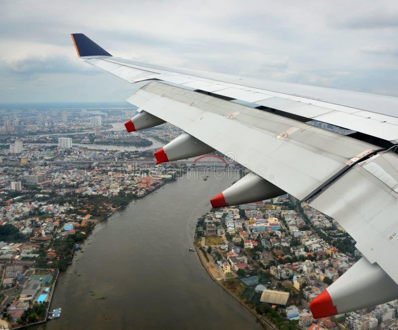 Εναέρια άποψη του αεροπλάνου που μπαίνει σε το έδαφος πέρα από τη πόλη Χο Τσι Μινχ στοκ φωτογραφίες