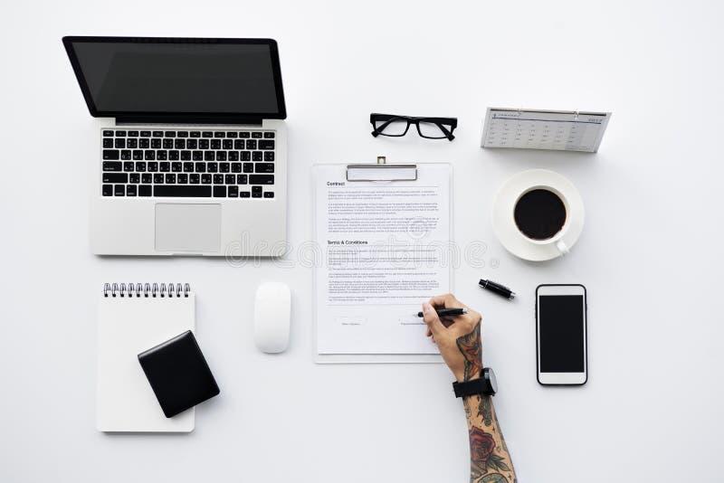 Εναέρια άποψη του επιχειρηματία που υπογράφει το χώρο εργασίας εγγράφου στοκ εικόνες