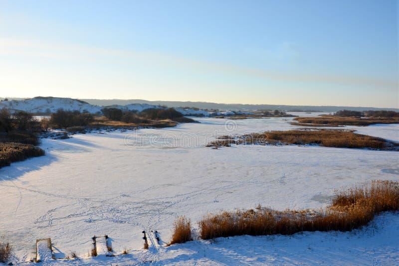 Εναέρια άποψη του ηλιοβασιλέματος πέρα από το χειμερινό χιονισμένο ποταμό στοκ εικόνα