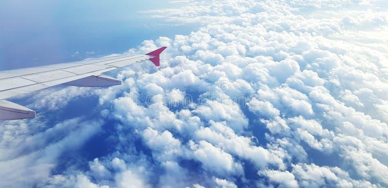 Εναέρια άποψη του φτερού αεροσκαφών ή αεροπλάνων που πετά στον ουρανό και τα όμορφα άσπρα σύννεφα στοκ εικόνες