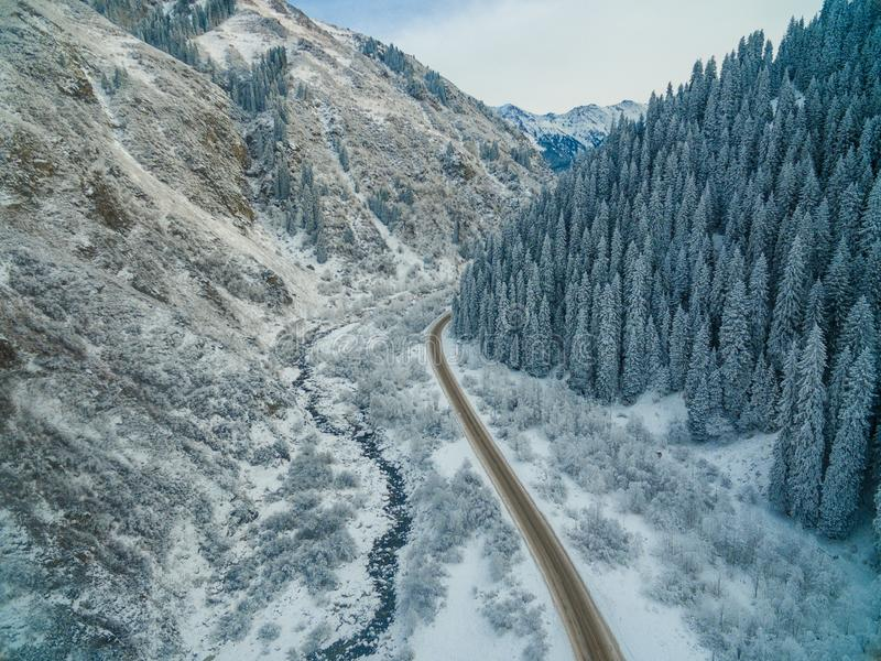 Εναέρια άποψη του χιονώδους δάσους με έναν δρόμο Συλλήφθείτε άνωθεν με έναν κηφήνα στοκ φωτογραφίες