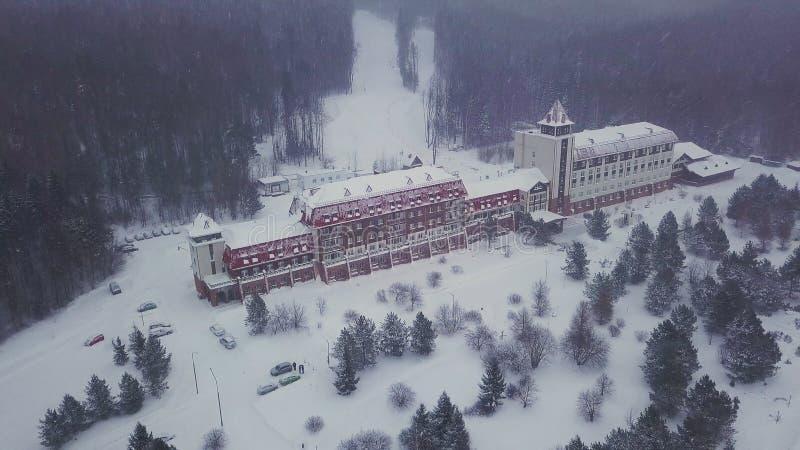 Εναέρια άποψη του όμορφου κτηρίου μεταξύ των δέντρων στα βουνά που καλύπτονται από το χιόνι r Όμορφο ξενοδοχείο στο χιονοδρομικό  στοκ φωτογραφία με δικαίωμα ελεύθερης χρήσης