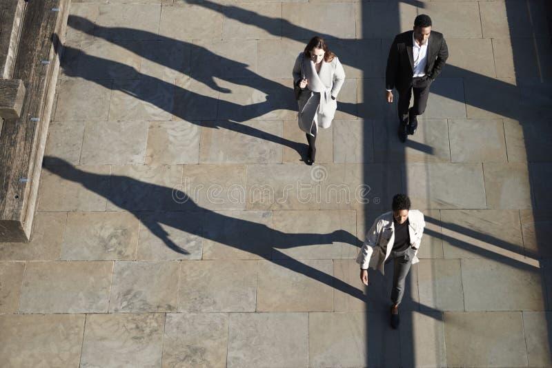 Εναέρια άποψη τριών υπαλλήλων που περπατούν σε μια ηλιόλουστη αστική οδό, οριζόντια στοκ φωτογραφίες με δικαίωμα ελεύθερης χρήσης