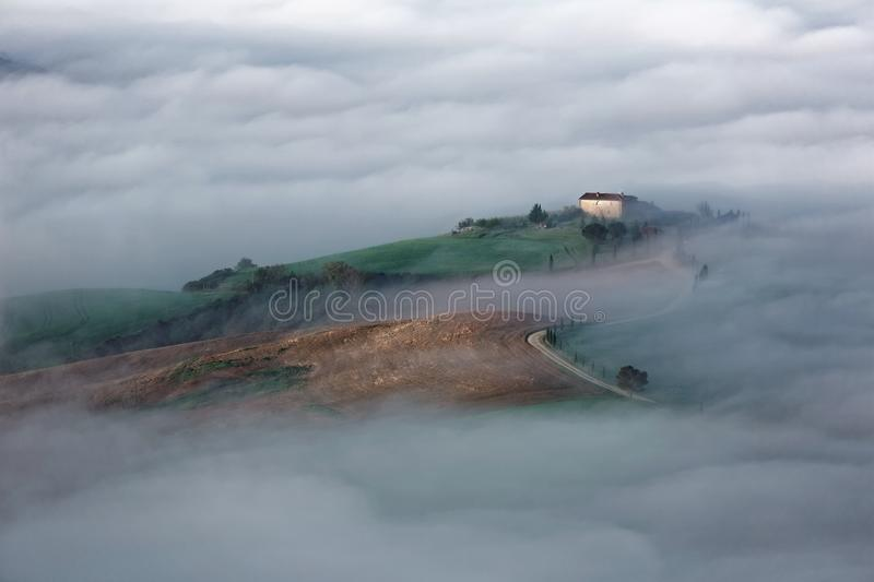 Εναέρια άποψη των αγροικιών κορυφών υψώματος & των δέντρων κυπαρισσιών στην Τοσκάνη σε ένα ομιχλώδες πρωί ~ άνοιξη στοκ εικόνες