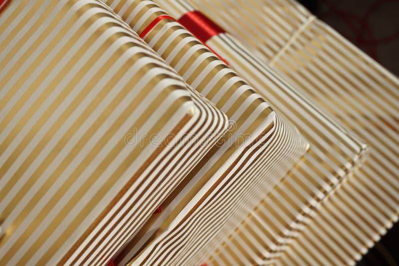 Εναέρια άποψη των ακρών των συσκευασιών δώρων στο άσπρο και χρυσό ευθυγραμμισμένο τυλίγοντας έγγραφο ως σύμβολο υποβάθρου των Χρι στοκ εικόνα