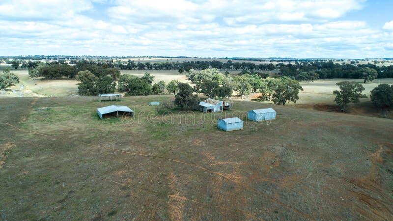 Εναέρια άποψη των γεωργικών αγροτικών υπόστεγων και των κόλπων αποθήκευσης σανού στο καλλιεργήσιμο έδαφος με τα δέντρα γόμμας ευκ στοκ εικόνα με δικαίωμα ελεύθερης χρήσης