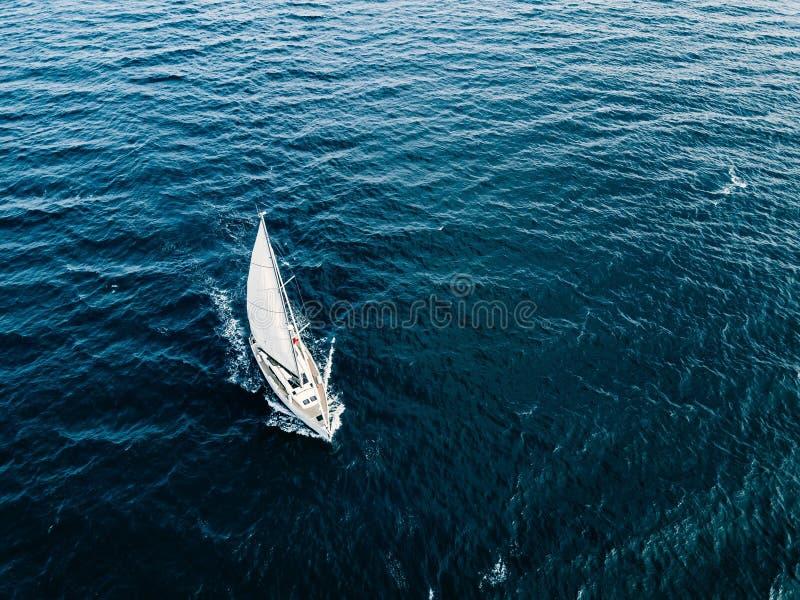 Εναέρια άποψη των πλέοντας γιοτ σκαφών με τα άσπρα πανιά στη βαθιά μπλε θάλασσα στοκ εικόνα με δικαίωμα ελεύθερης χρήσης