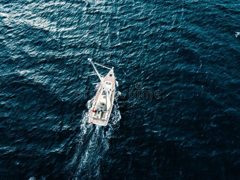 Εναέρια άποψη των πλέοντας γιοτ σκαφών με τα άσπρα πανιά στη βαθιά μπλε θάλασσα στοκ φωτογραφία