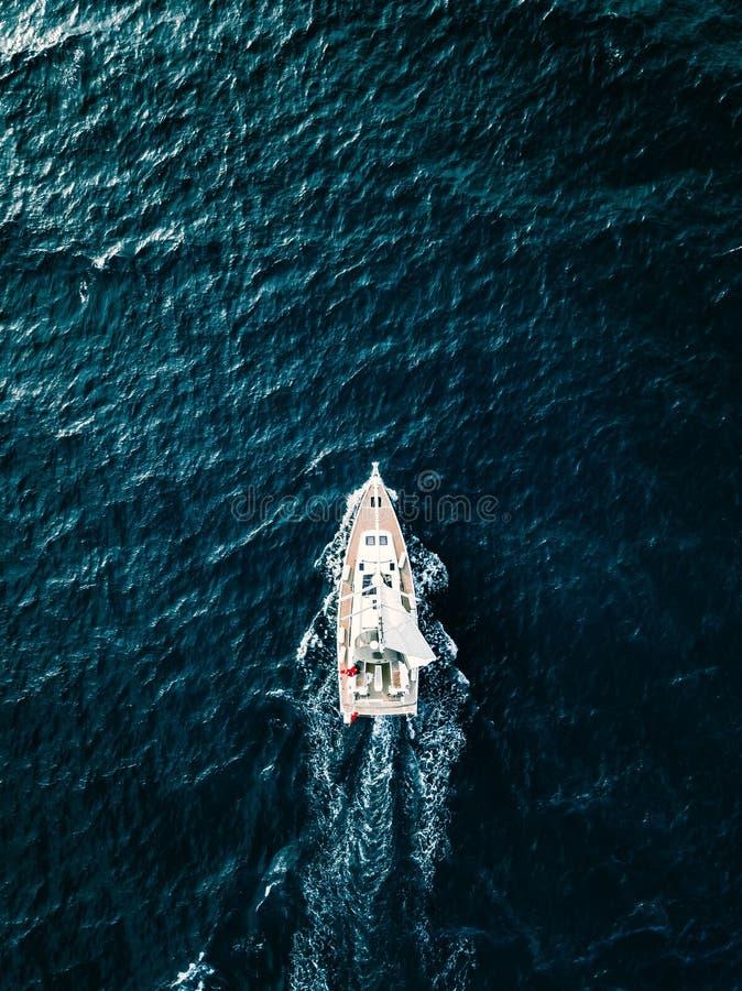 Εναέρια άποψη των πλέοντας γιοτ σκαφών με τα άσπρα πανιά στη βαθιά μπλε θάλασσα στοκ εικόνα