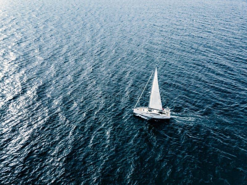 Εναέρια άποψη των πλέοντας γιοτ σκαφών με τα άσπρα πανιά στη βαθιά μπλε θάλασσα στοκ φωτογραφίες